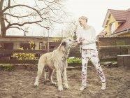 Frau Fütterung Irish Wolfhound im freien — Stockfoto