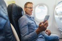Зрелый человек, сидя в самолете, глядя на его смартфон — стоковое фото
