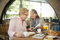 Smiling senior couple reading book and having breakfast in a cafe — Stock Photo