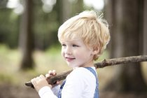 Portrait of smiling little boy with branch — Stock Photo