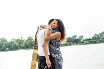 Young couple embracing by the riverside — Stock Photo