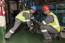 Взрослая кавказская команда работает в машинном отделении на корабле — стоковое фото