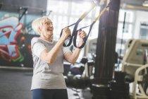 Happy senior woman in gym doing suspension training — Stock Photo