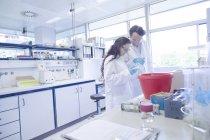 Tecnici di laboratorio che discutono il campione in laboratorio — Foto stock