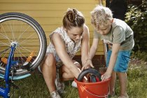Mother and son repairing bicycle together — Stock Photo