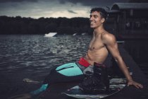 Relaxed young wakeboarder sitting at lakeshore — Stock Photo