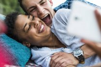 Laughing young couple lying outdoors holding a cell phone — Stock Photo