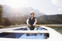 Germany, Bavaria, Eibsee, man in rowing boat on the lake — Stock Photo