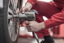 Car mechanic at work in repair garage, changing tires, impact driver — Stock Photo