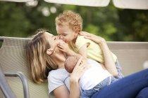 Jeune maman avec ses deux filles peu sur une balançoire de verrière — Photo de stock