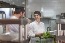 Male and female chef with fresh ingredients in restaurant kitchen — Stock Photo