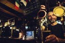 Man tapping beer in an Irish pub — Stock Photo