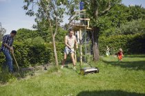 Family gardening together with lawn mower and garden tool — Stock Photo