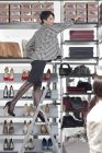 Shop assistant in shoe shop standing on stepladder — Stock Photo