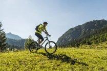 Österreich, Tirol, Tannheimer Tal, junger Mann mit Mountainbike in alpiner Landschaft — Stockfoto