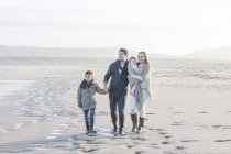 Young couple with two children walking on the beach — Stock Photo