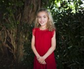 Portrait of a smiling little girl wearing a red dress — Stock Photo