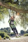 Man doing CrossFit exercise on rings hanging on tree trunk — Stock Photo