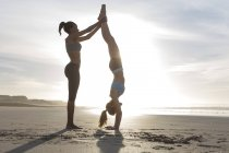 South Africa, Cape Town, young woman helping her friend doing handstand on the beach — Stock Photo