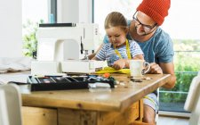 Father and daughter at home using sewing machine — Stock Photo
