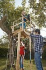 Family playing in garden at tree house — Stock Photo
