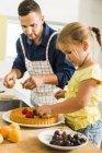 Батько і дочка на кухні, готуючи фруктовий торт — стокове фото