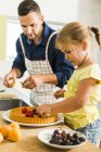 Father and daughter in kitchen preparing fruit cake — Stock Photo