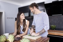 Smiling couple face to face i their modern kitchen — Stock Photo