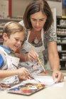 Ragazzino in una classe d'arte con il suo insegnante di pittura — Foto stock