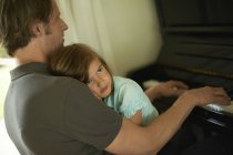 Father playing piano with daughter on his lap — Stock Photo