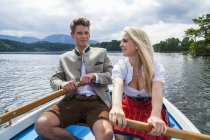 Germany, Bavaria, young couple wearing traditional clothes rowing together on Staffelsee — Stock Photo