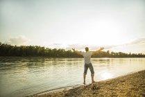 Vue arrière de l'homme debout au bord de la rivière avec les bras tendus — Photo de stock