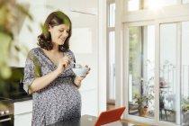 Беременная женщина с чашей мюсли на кухне — стоковое фото
