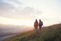 Austria, Tirol, pareja de senderismo en Unterberghorn al amanecer - foto de stock