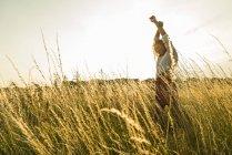 Junge Frau mit erhobenen Armen in Bereichen mit hohen grass — Stockfoto