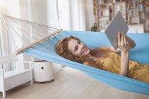 Frau liegt in Hängematte und benutzt Tablette — Stockfoto