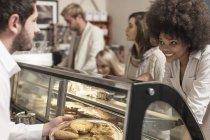 Junge Frau, die Kuchentheke in Coffee-Shop Kuchen auswählen — Stockfoto