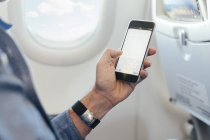Man sitting on an airplane holding smartphone — Stock Photo