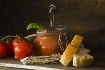 Frische Tomatensuppe mit Basilikum im Glas, Tomaten und Weißbrot auf Holz zu konservieren — Stockfoto