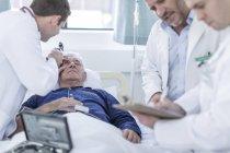 Лікарі, вивчаючи пацієнта у лікарні — стокове фото