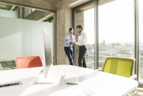 Two young businessmen talking at the window in office — Stock Photo