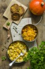 Veggie burgers with bowls of prepared pumpkin, gnocchi and Hokkaido pumpkin — Stock Photo