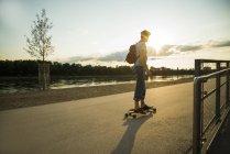 Homme debout sur skateboard dans le crépuscule du soir — Photo de stock