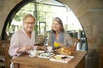 Smiling senior couple having breakfast in a cafe — Stock Photo