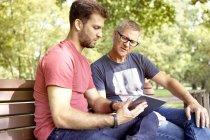 Due uomini seduti su una panchina del parco a guardare tablet digitale — Foto stock