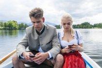 Retrato de Alemania, Baviera, de pareja de jóvenes sentados en un bote de remos en Staffelsee mirando sus celulares - foto de stock