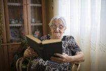 Mulher sênior lendo um livro na cadeira em casa — Fotografia de Stock