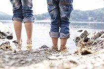 Gros plan de deux enfants debout au bord du lac — Photo de stock