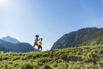 Autriche, jeune couple de Tyrol, vallée de Tannheim, faire du jogging dans le paysage alpin — Photo de stock