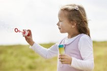 Little girl holding bubble ring and blowing soap bubbles — Stock Photo